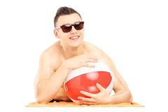 Smiling guy lying on a beach towel and holding a ball Royalty Free Stock Image