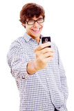 Smiling guy making picture by phone. Young man laughing and filming something funny on his mobile phone isolated on white background Stock Photo