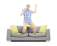 Smiling guy with microphone singing and standing on a sofa Royalty Free Stock Image