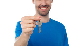 Smiling guy offering house key Royalty Free Stock Photo