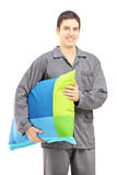 Smiling guy in pajamas holding a pillow Stock Photos