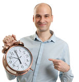 Smiling guy pointing on a big alarm clock Stock Photography