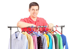 A smiling guy posing on a hang rail full of clothes. Isolated on white background Royalty Free Stock Photo