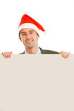 Smiling guy in Santa hat holding blank billboard Stock Images