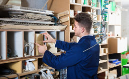 Smiling guy searching for items in storage at workplace Stock Photo