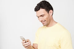 Smiling guy sending a text message. Casual guy reading a funny text message Royalty Free Stock Image