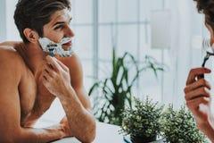 Smiling guy shaving his beard by razor royalty free stock image
