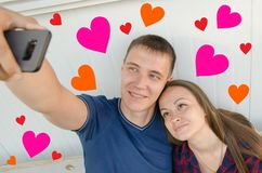 Smiling guy with short haircut in blue T-shirt and girl with dark long hair in checkered shirt take a selfie on the phone and royalty free stock photos