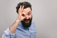 Smiling guy showing OK gesture at camera royalty free stock images
