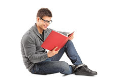 Smiling guy sitting on a floor and reading a book Royalty Free Stock Image