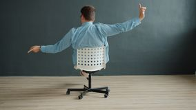 Smiling guy spinning on office chair pointing at camera on dark gray background