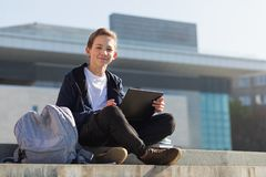 Smiling guy studying outdoor with laptop, sitting on the stairs royalty free stock images