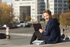 Smiling guy studying outdoor with laptop, sitting on the stairs and looking at camera royalty free stock photo