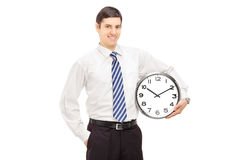 Smiling guy in suit holding a clock Royalty Free Stock Photo