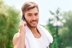 Smiling guy talking on phone. Having nice conversation with sweetheart. Positive handsome guy holding mobile phone and talking on it Royalty Free Stock Photo