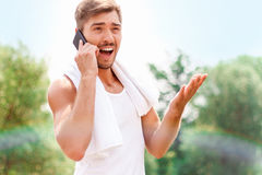 Smiling guy talking on phone. What an astonishing news. Pleasant young man holding mobile phone and talking on it while expressing surprise Stock Images