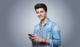 Smiling guy texting with smartphone Royalty Free Stock Photo