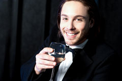 Smiling guy in tuxedo drinking cocktail Royalty Free Stock Images