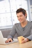 Smiling guy using laptop computer Royalty Free Stock Photos