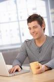 Smiling guy using laptop computer Royalty Free Stock Photos
