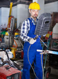 Smiling guy using welder for construction work. Young smiling guy using welder for construction work at the workshop Stock Image