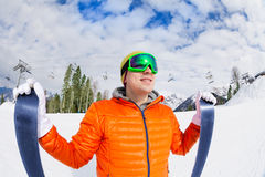 Smiling guy wearing mask holding ski in winter Royalty Free Stock Photo