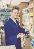 Smiling  guy woodworker searching for items in storage Royalty Free Stock Photo