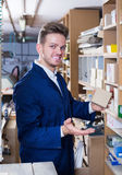 Smiling  guy woodworker searching for items in storage Royalty Free Stock Image