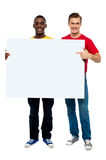 Smiling guys with white ad board Stock Photo