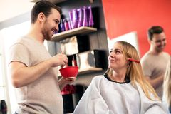 Smiling hair styling with his blonde costumer at beauty salon. Preparing for hait dye Royalty Free Stock Photos