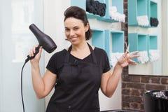 Smiling hairdresser holding hair equipment Stock Photos