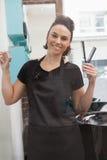 Smiling hairdresser holding hair equipment Stock Image