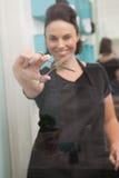 Smiling hairdresser holding hair equipment Royalty Free Stock Photo