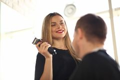 Smiling Hairdresser Using Electric Razor to Client. Professional Hairstylist Holding Sharp Shaver in Hand. Young Barber Shave Man in Barbershop. Female Stylist royalty free stock photos