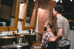 Smiling hairstylist and plesed man client looking in mirror Stock Images