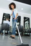 Smiling hairstylist sweeping hair clippings on floor in salon. Smiling hairstylist sweeping hair clippings on floor in her salon Royalty Free Stock Images
