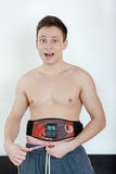 Smiling Half-naked handsome young man with an electrical device Stock Image