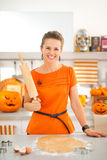 Smiling halloween dressed woman with rolling pin in kitchen Stock Photos