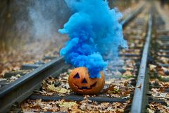 Smiling halloween pumpkin with bright blue smoke on the rails in the forest Stock Photo
