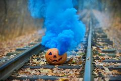 Smiling halloween pumpkin with bright blue smoke on the rails in the forest Stock Photos
