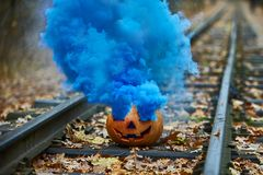 Smiling halloween pumpkin with bright blue smoke on the rails in the forest Royalty Free Stock Photos