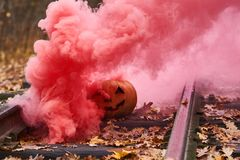Smiling halloween pumpkin with bright red smoke on the rails in the forest. Selective focus Stock Images