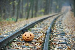 Smiling halloween pumpkin on the rails in the forest Royalty Free Stock Photos