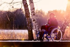 Smiling handicapped woman on wheelchair in winter Royalty Free Stock Image