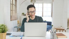 Free Smiling Handsome Asian Businessman Working Remotely From Home. He Is Speaking On The Mobile Phone Stock Photos - 216661143