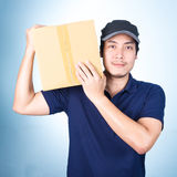 Smiling handsome asian delivery man giving and carrying parcel o Royalty Free Stock Photos