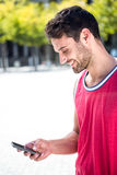 Smiling handsome athlete sending a text Royalty Free Stock Photo