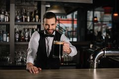 smiling handsome bartender holding glass stock photo