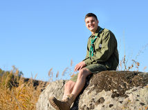 Smiling Handsome Boy Scout Sitting on the Rock Stock Images
