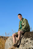 Smiling Handsome Boy Scout Sitting on the Rock Stock Photography